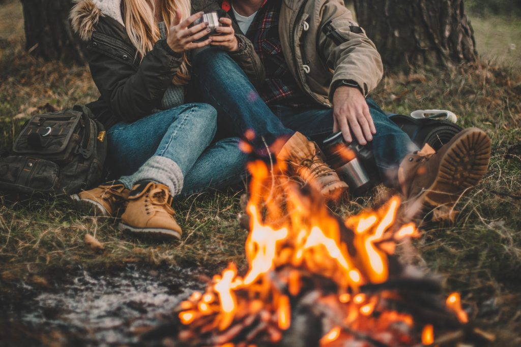 couple camping in the forest and relaxing near campfire